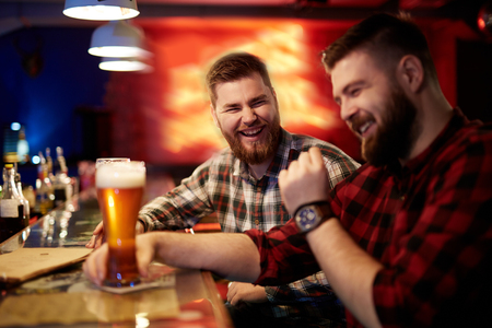adult entertainment: Friendly young men with beer talking in pub