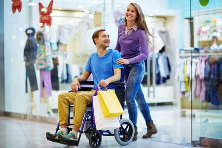 going out: Caregiver and guy in wheelchair going out of clothing department Stock Photo