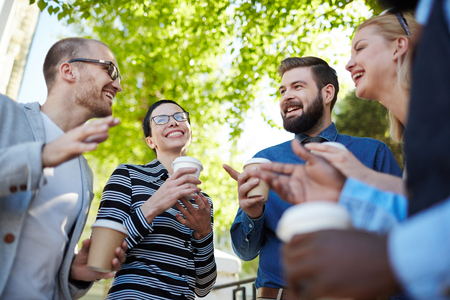 Group of happy entrepreneurs having drink and discussing ideas in a start-up meeting outdoors