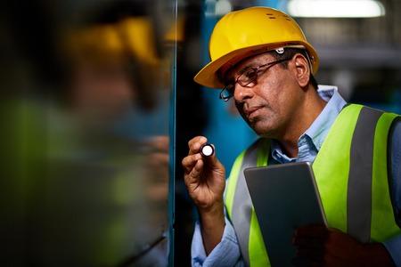 executive helmet: Mature repairman in helmet and uniform working at plant Stock Photo
