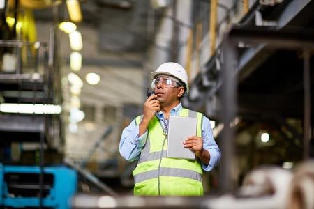 executive helmet: Mature foreman speaking on walkie-talkie at work Stock Photo