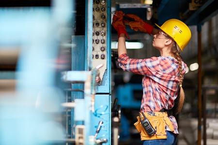 Vrouwelijke elektricien of technicus met schroevendraaier reparatie machine op plant