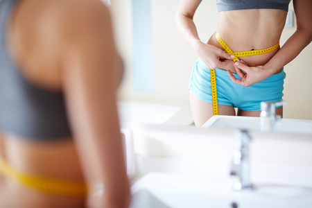 fatness: Young woman measuring her waist in front of mirror