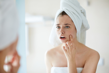Anxious girl looking at pimple on her cheek in mirror