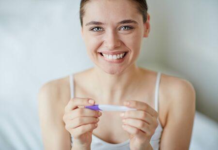 femenino feliz con la prueba de embarazo lookng a la cámara