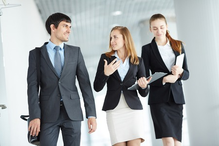 executive women: Colleagues in formalwear interacting after work