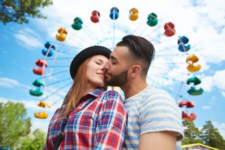 romantic date: Amorous young couple kissing on background of amusement