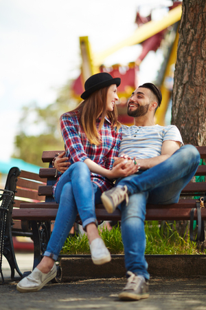 couples hug: Young man and woman talking on bench in park