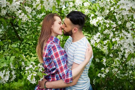 amorous woman: Happy amorous couple embracing in blooming garden Stock Photo