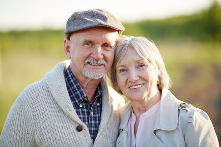 toothy smiles: Retired husband and wife looking at camera with toothy smiles