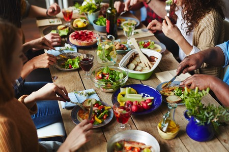 Hungry people eating appetizing vegetarian dinner