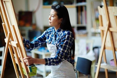 芸術のスタジオのイーゼルで描く芸術の創造的な学生 写真素材
