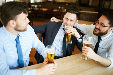 businesspeople: Relaxed businessmen drinking beer after work in pub