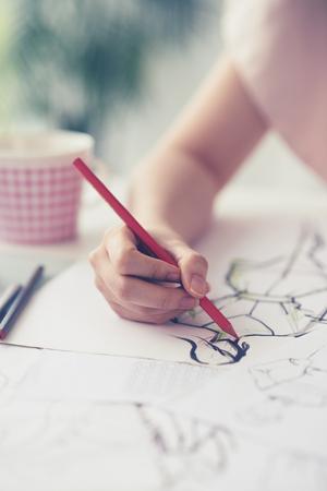 dressmaker: Close-up of dressmaker drawing fashion sketch Stock Photo