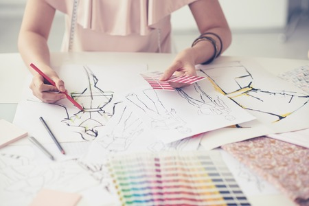 Weibliche Modedesigner arbeiten an ihren Entwürfen im Studio Standard-Bild