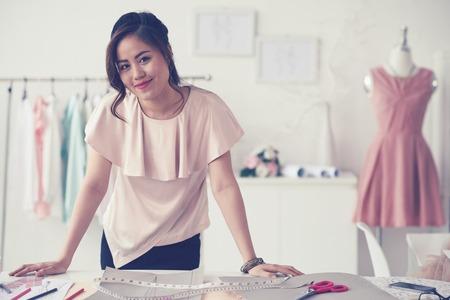 Retrato de joven modista de pie en el taller