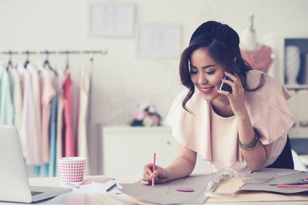 Mladý módní návrhář dělat vzor a mluví po telefonu