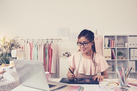 Jeune femme dans des lunettes dessinant sur son ordinateur portable en atelier