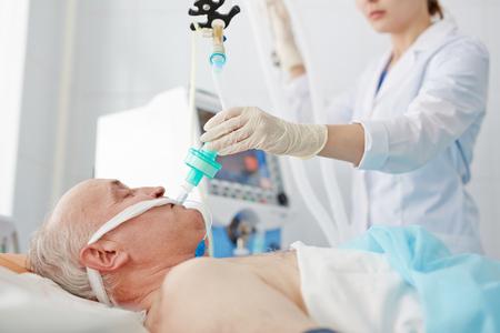Nurse intruding endotracheal tube into senior mans mouth Stock Photo