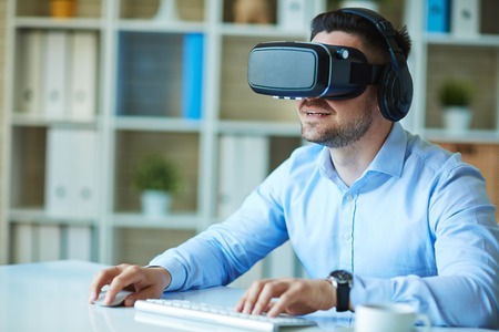 Businessman gaming with vr headset in office