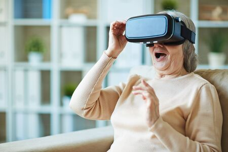 simulations: Senior woman surprising vr simulator Stock Photo