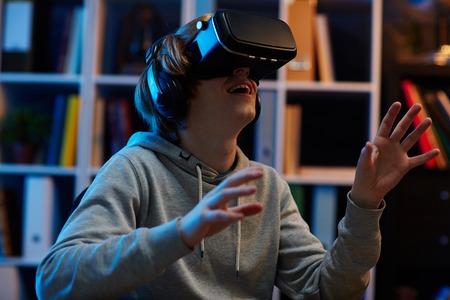 Teenager using vr glasses at night
