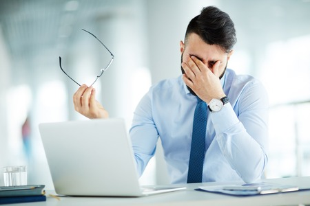 Businessman rubbing eyes at laptop 스톡 콘텐츠