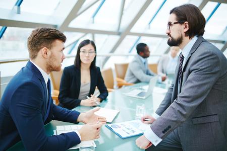 preguntando: El hombre de negocios haciendo preguntas a líder en la reunión
