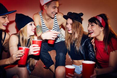 ecstatic: Ecstatic young people with drinks talking in bar Stock Photo