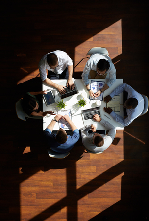 business people meeting: Medium group of co-workers discussing data and new ideas or project by table Stock Photo