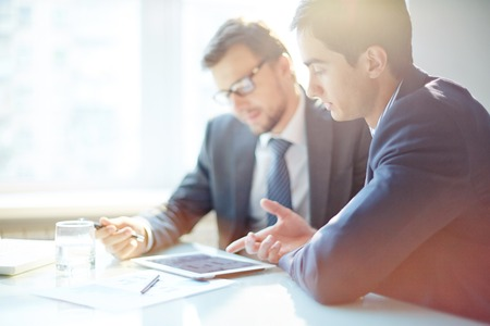 information point: Two contemporary businessmen discussing data at meeting Stock Photo