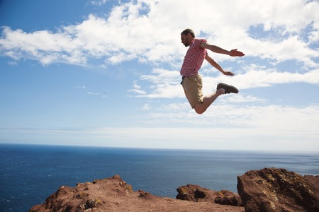 cliff jumping: Energetic guy jumping over cliff by seaside