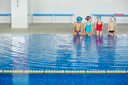 swim: Group of kids in swimwear talking in swimming pool
