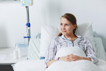 Jolie patient assis dans son lit Banque d'images