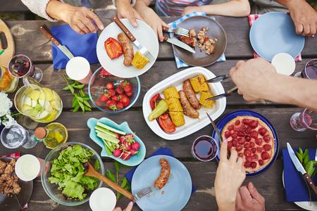chorizos asados: Manos de vegs alimentarios familiares y salchichas a la parrilla en la comida campestre