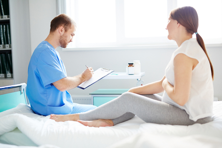 obstetrician: Obstetrician making notes in medical card of pregnant woman