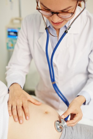 obstetrician: Obstetrician examining belly of pregnant patient