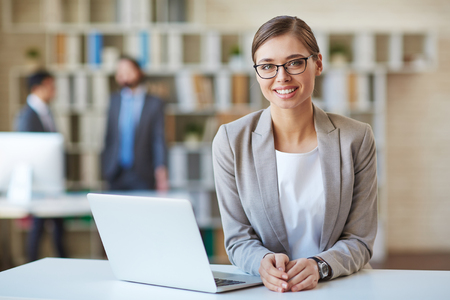 Happy young employee looking at camera