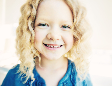 Happy girl with wavy blond hair looking at camera photo