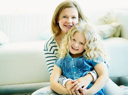 mother love: Mother and her daughter looking at camera at home