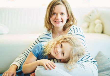 Adorable girl and her mother spending time at home photo
