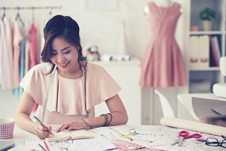 Glimlachend charmante jonge vrouw naaister tekening schetsen en patronen aan de tafel