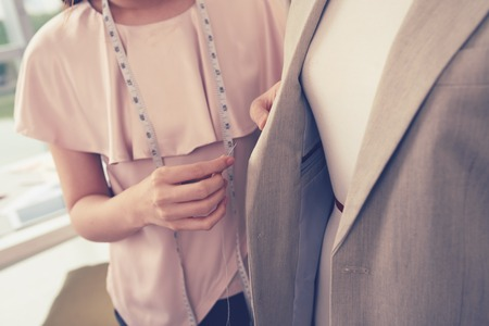 Close-up of fashion designer working with jacket