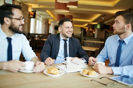 new contract: Potential business partners discussing terms of new contract while having drinks and croissants in cafe