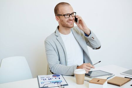 work addicted: Happy young businessman calling at workplace