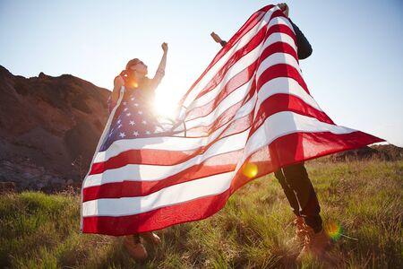 julio: Feliz patriotas con la bandera americana y las manos levantadas