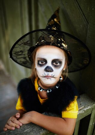 painted face: Little witch with painted face looking at camera