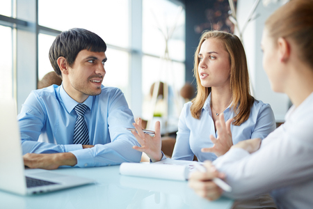explaining: Young businesswoman explaining her idea to co-workers at briefing