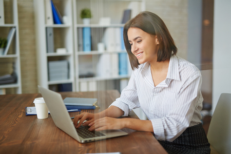 attractive businesswoman: Attractive businesswoman typing at workplace Stock Photo