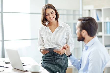 men talking: Pretty young woman with laptop listening to her employer